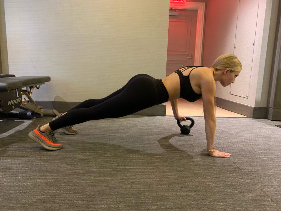 woman doing Kettlebell Plank Pass