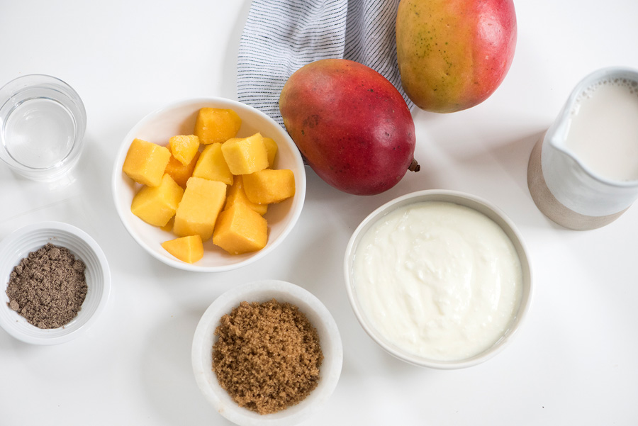 sliced mango in a bowl with ingredients to make smoothie