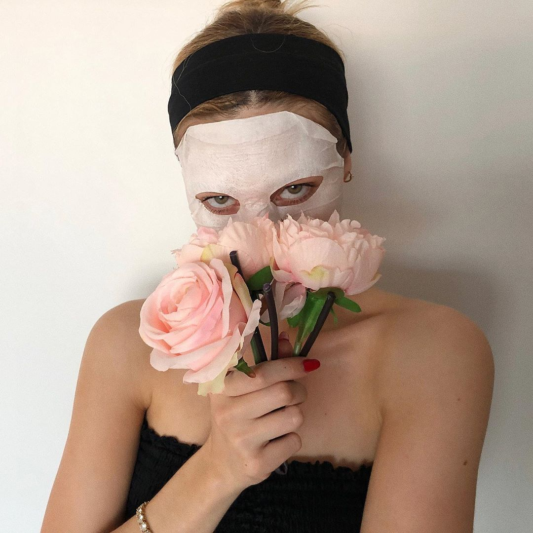 woman wearing sheet mask with flowers
