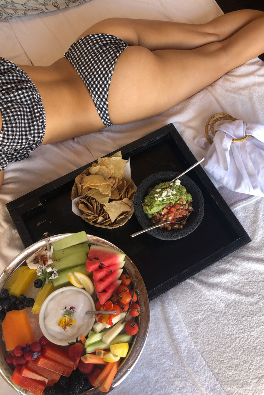 woman laying in cabana with fruit platter