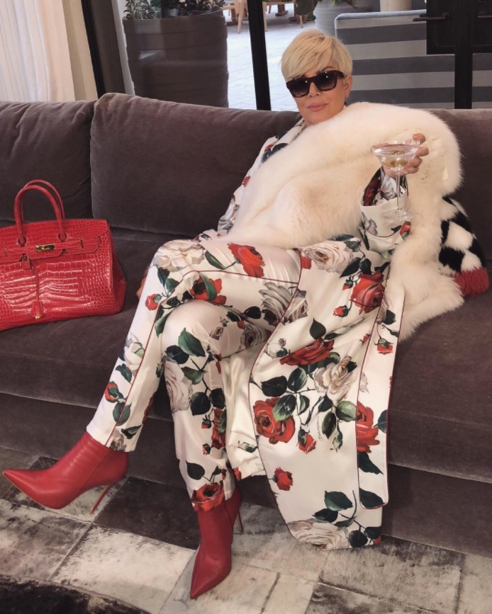 kris jenner wearing printed silk set on couch with cocktail
