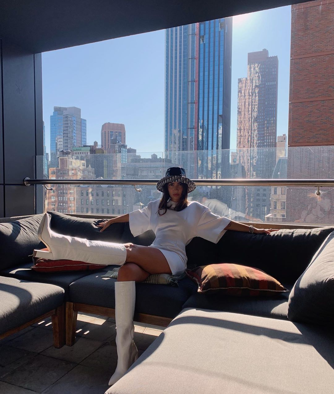 woman posing on hotel couch wearing all white and white boots