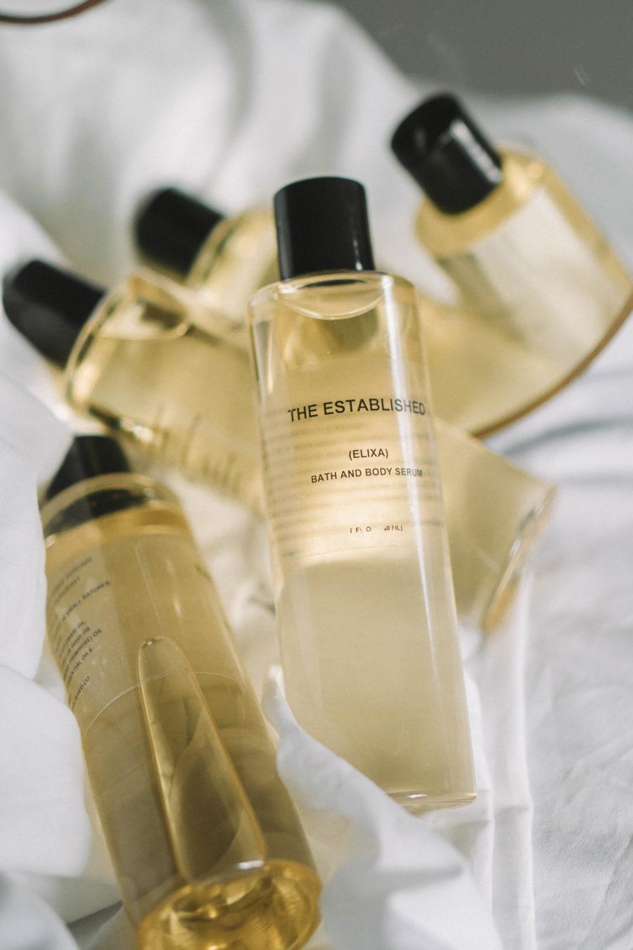 The Established Elixa Bath and Body Serum bottles