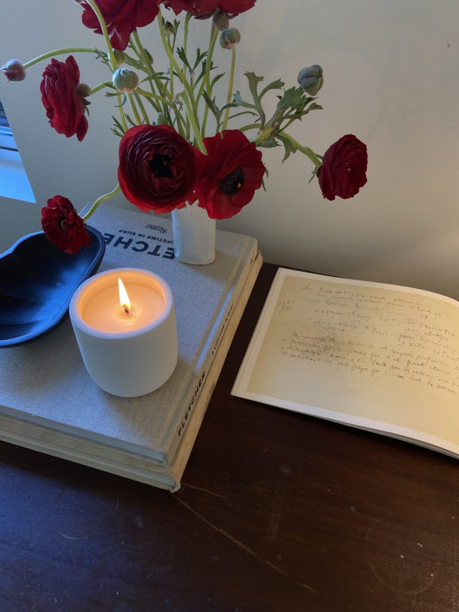 dehv candle on desk with red flowers