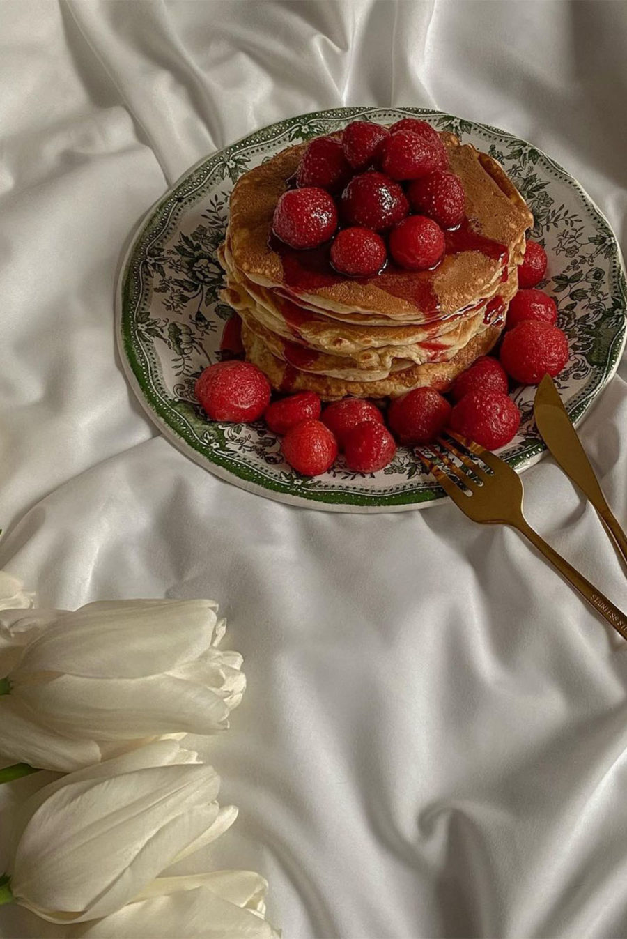 Pancakes with flowers, raspberries on bed