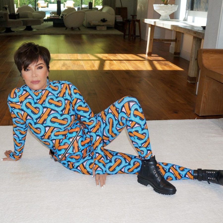 Kris Jenner posing on the ground in colorful outfit