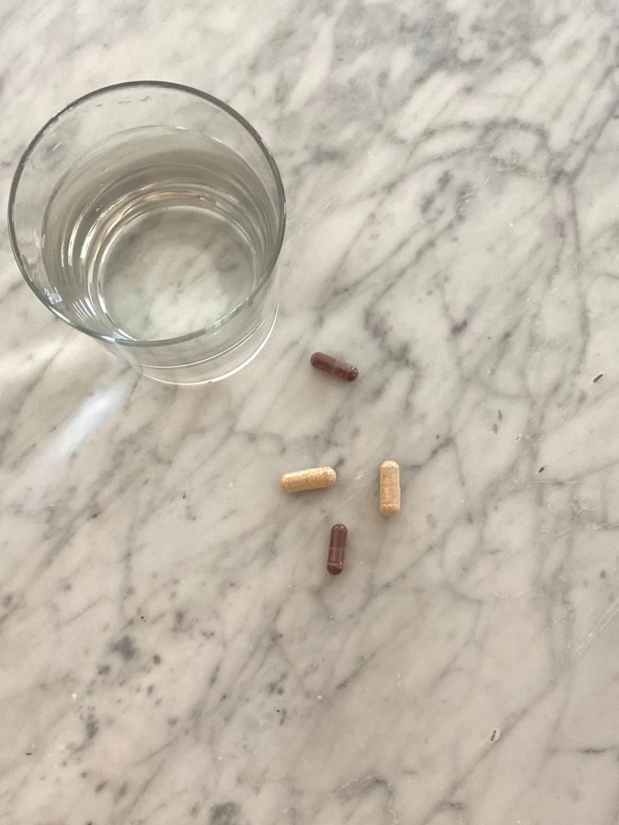 Glass of water with supplements on counter