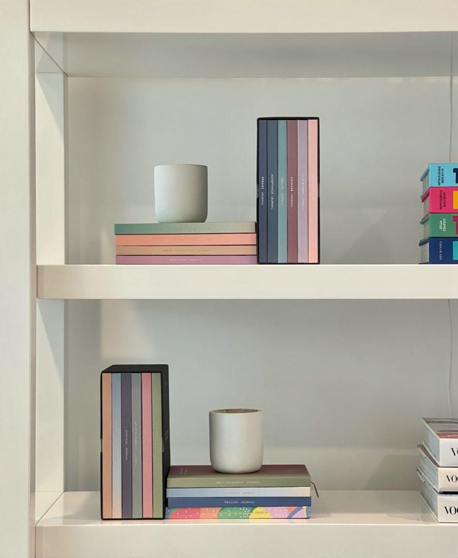 pretty journals on white bookshelf