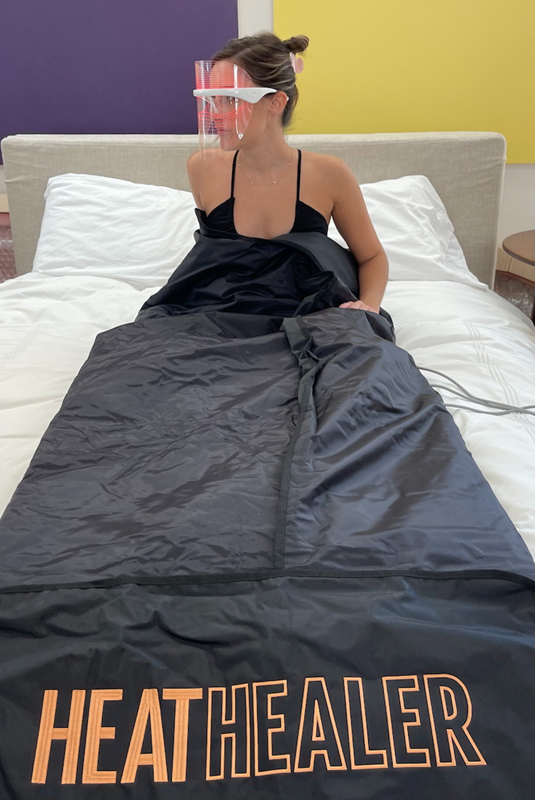 woman using Infrared Sauna Blanket in bed and wearing LED light shield mask