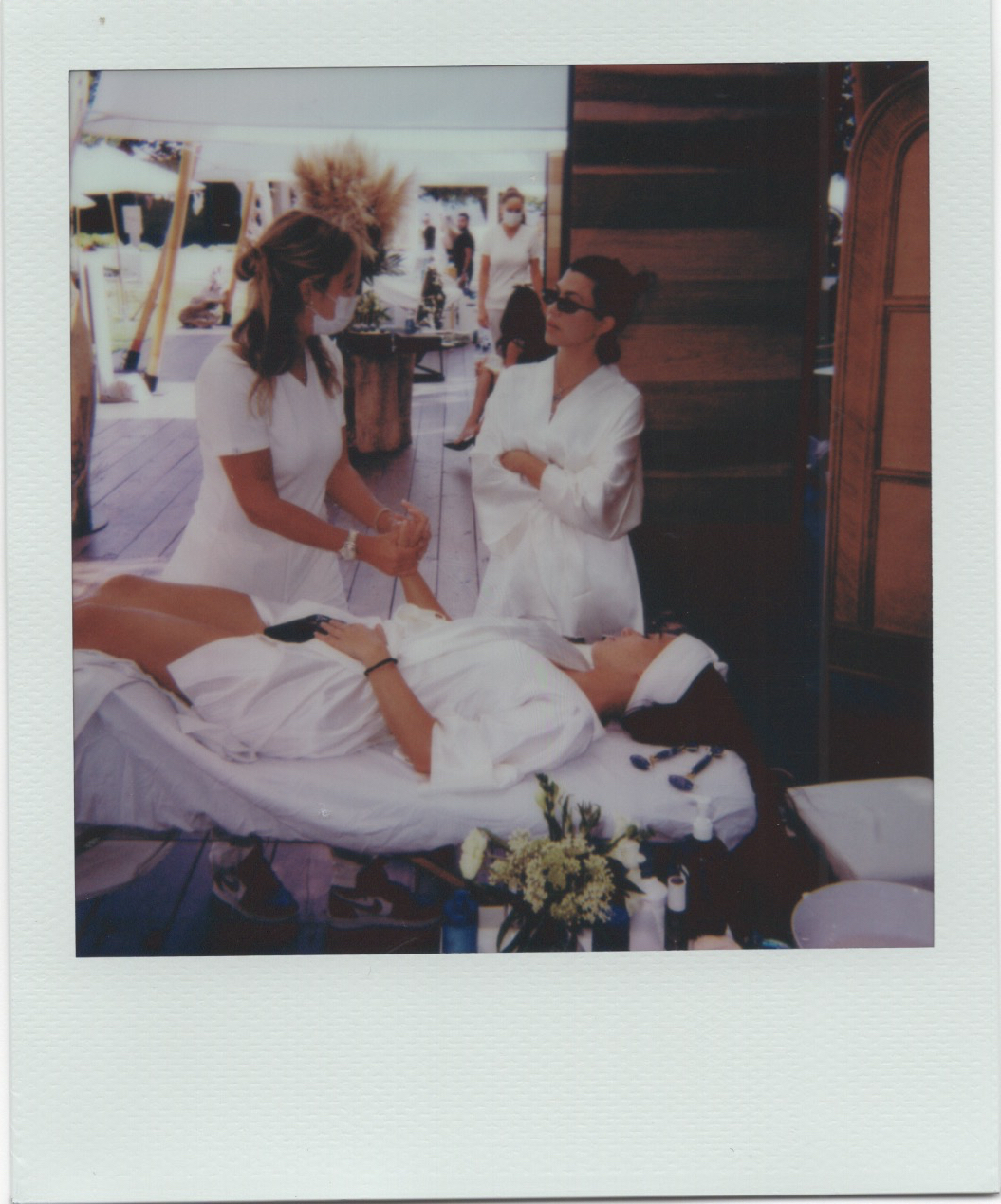 kourtney kardashian in white robe at poolside poosh event talking to person getting massage